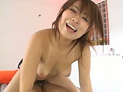 Japanese slut sucks on a cock while she rides another